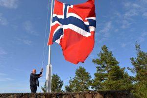 Leder i U3A heiser flagget til topps på Varden for første U3A foredrag der